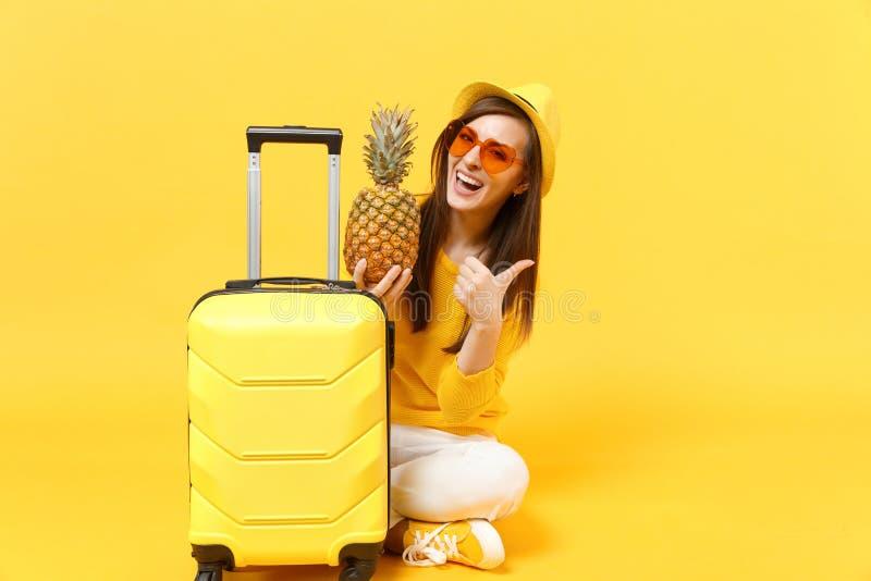 Femme de touristes de voyageur drôle dans le pouce d'apparence de chapeau, fruit mûr frais d'ananas de prise d'isolement sur jaun images libres de droits