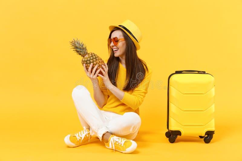 Femme de touristes de voyageur joyeux dans des vêtements d'été, fruit mûr frais d'ananas de prise de chapeau d'isolement sur jaun photographie stock libre de droits