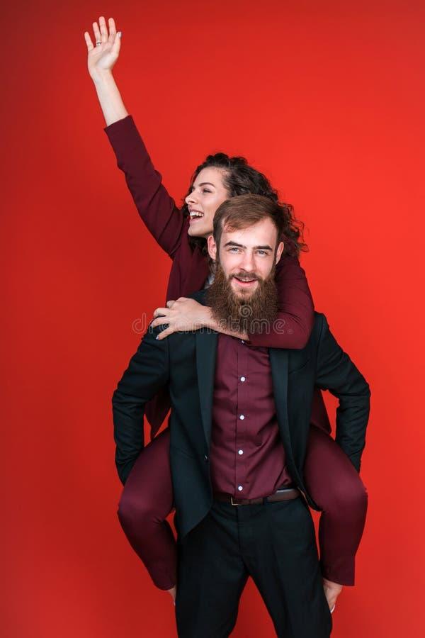 Femme de transport d'homme sur arrière et le sourire photo libre de droits
