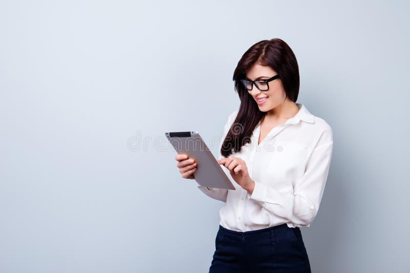 Femme de travailleur assez jeune dans se tenir formel d'habillement et en verre photo libre de droits