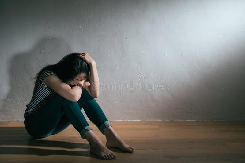 Femme de tristesse de dépression s'asseyant sur le plancher en bois photo libre de droits