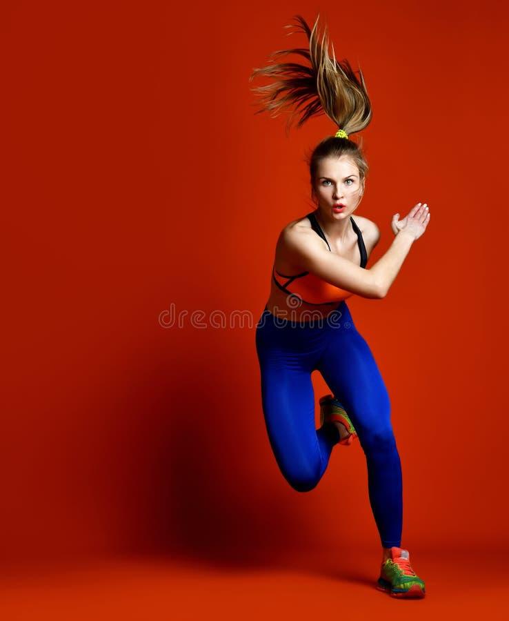 Femme de turbine d'isolement Pulser convenable fonctionnant de modèle de sport de forme physique d'isolement sur le fond rouge photographie stock libre de droits