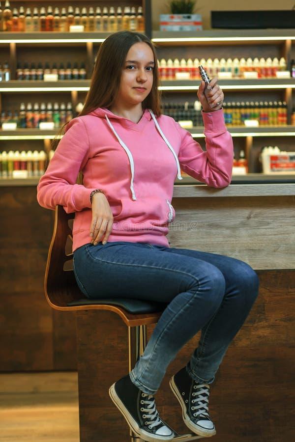 Femme de Vape Jeune fille mignonne dans le hoodie rose fumant une cigarette électronique photos stock