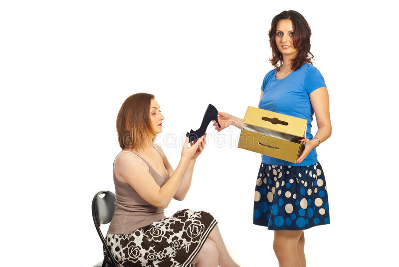 Femme de vendeur affichant la chaussure au client photos libres de droits