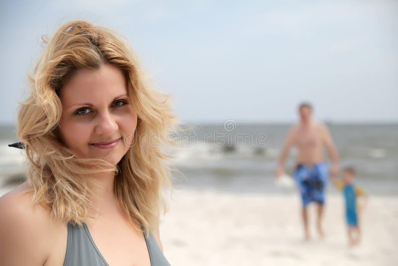 Femme de verticale en fonction sur la plage et le famille de t derrière elle images libres de droits