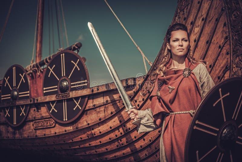 Femme de Viking avec l'épée et le bouclier se tenant près de Drakkar sur le bord de la mer photos libres de droits