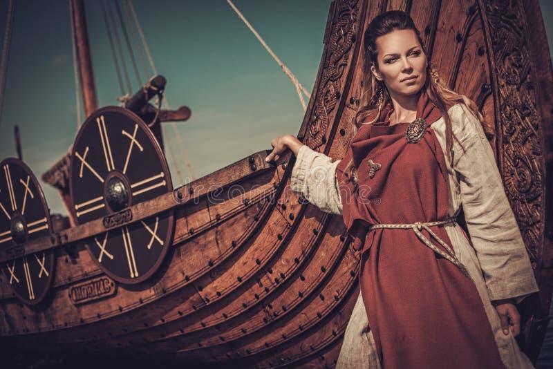 Femme de Viking se tenant près de Drakkar sur le bord de la mer images libres de droits