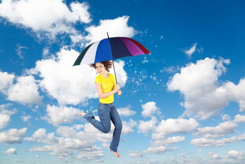 Femme de vol avec le parapluie sur le fond de ciel images libres de droits