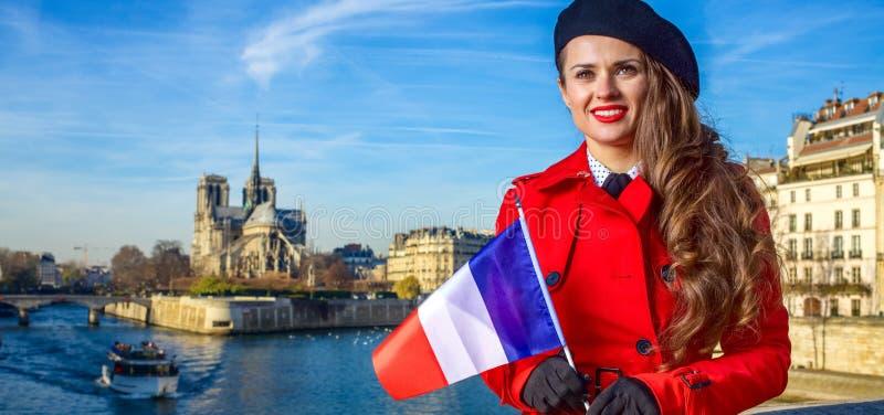 Femme de voyageur à Paris avec le drapeau français examinant la distance photographie stock