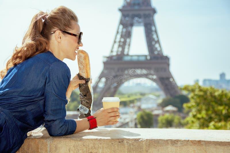 Femme de voyageur avec la tasse de café mangeant la baguette ayant l'excursion image stock