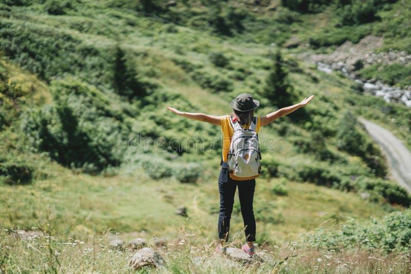 Femme de voyageur de liberté se tenant avec les bras augmentés et apprécier photos stock