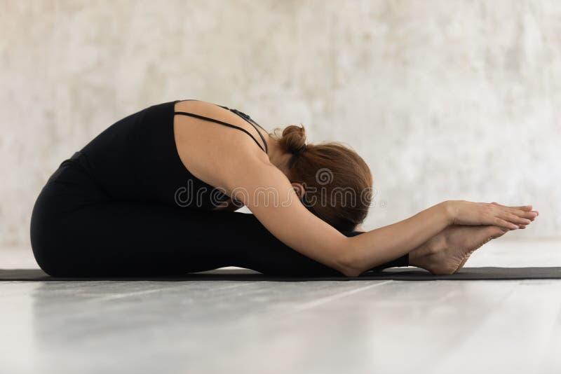 Femme de vue de côté faisant la pose en avant posée de courbure sur le tapis photos libres de droits