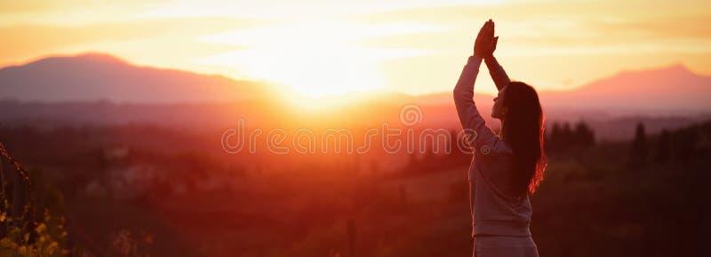 Femme de yoga m?ditant au coucher du soleil image stock
