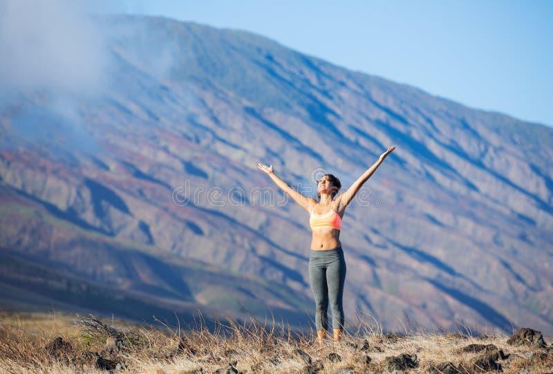 Femme de yoga pratiquant dans une plage photos stock