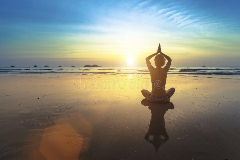 Femme de yoga s'asseyant dans la pose de lotus sur la plage avec la réflexion pendant le coucher du soleil photos libres de droits
