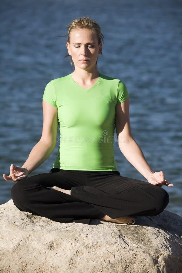 Femme de yoga s'asseyant par l'eau image stock
