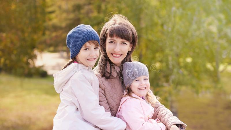 Femme de Youn avec deux filles outdoors Fond d'automne F?te des m?res photographie stock