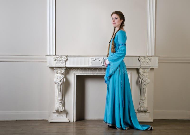 Femme de Yound dans la robe historique près de la cheminée photographie stock