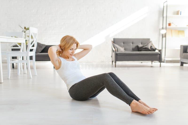 Femme de Yuong faisant l'exercice de matin dans le salon images stock