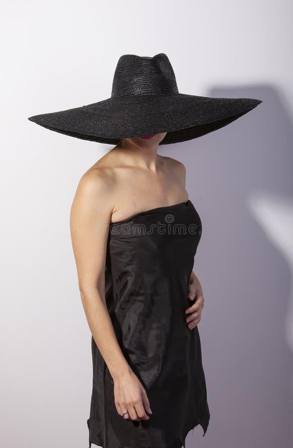 Femme debout utilisant le costume noir et le chapeau noir, rétro mode photographie stock libre de droits