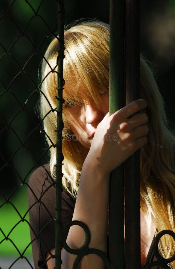 Femme derrière la frontière de sécurité en métal images libres de droits