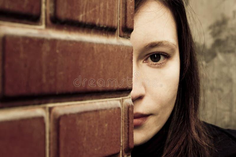 Femme derrière le brickwall images libres de droits