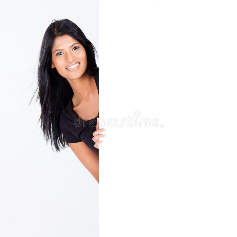 Femme derrière le panneau blanc photo stock