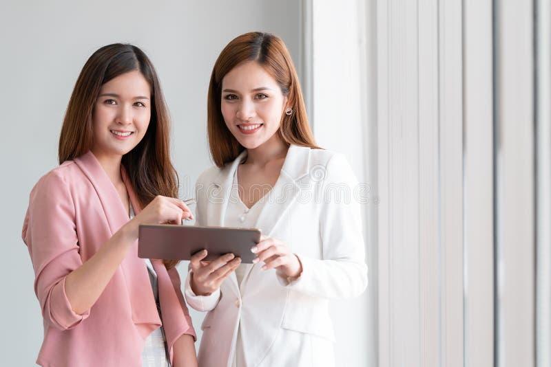 Femme des affaires deux discutant sur le comprimé regardant l'appareil-photo photo stock