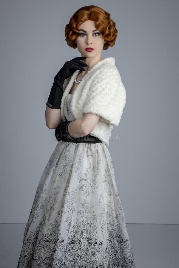 femme des années 1950 dans la robe noire et blanche utilisant une étole de fourrure photos stock