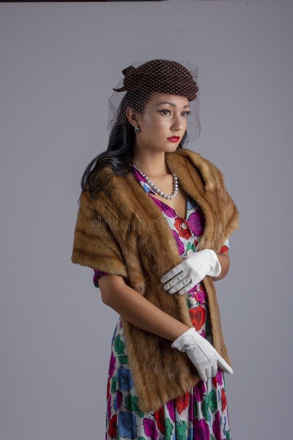 femme des années 1950 dans une robe colorée, le chapeau avec un voile et une étole de fourrure contre un contexte blanc images stock