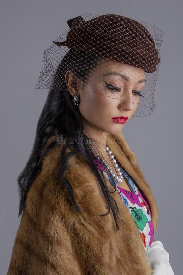 femme des années 1950 dans une robe colorée, le chapeau avec un voile et une étole de fourrure contre un contexte blanc photographie stock libre de droits