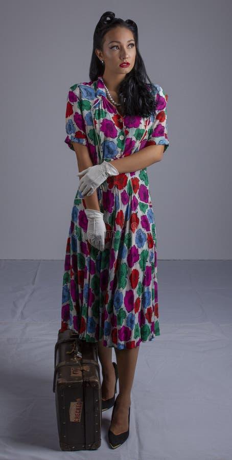 femme des années 1950 dans une robe colorée se tapissant près d'une valise contre un contexte blanc photographie stock libre de droits