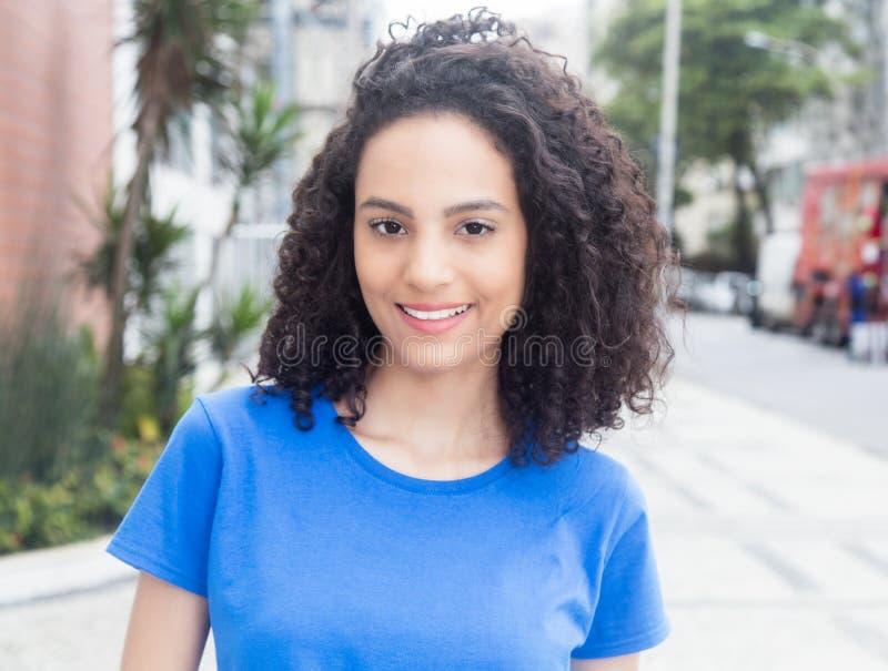 Femme des Caraïbes riante avec la chemise bleue dans la ville images libres de droits