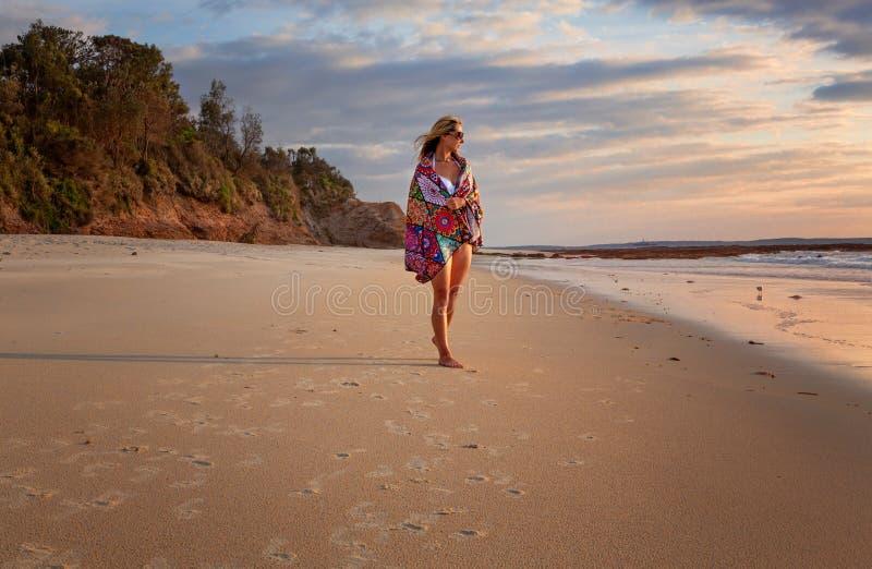 Femme des vacances marchant le long de la plage images stock