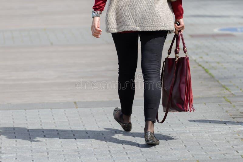 Femme descendant la rue avec un sac photo libre de droits