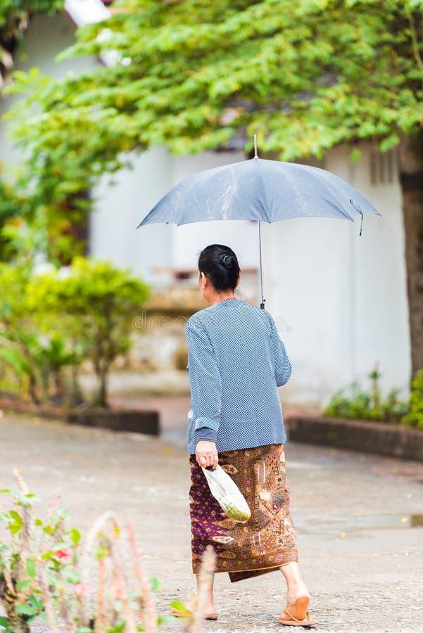 Femme descendant la rue sous un parapluie dans Louangphabang, Laos vertical images stock