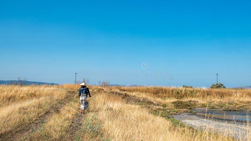 Femme descendant le chemin par des prairies avec le grand ciel bleu photographie stock