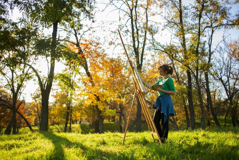 Femme dessinant une image sur la toile sur un chevalet dans la nature, une fille avec une brosse et une palette des peintures dan images stock