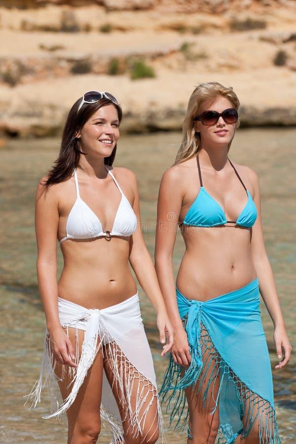 Femme deux attirante marchant sur la plage photos libres de droits
