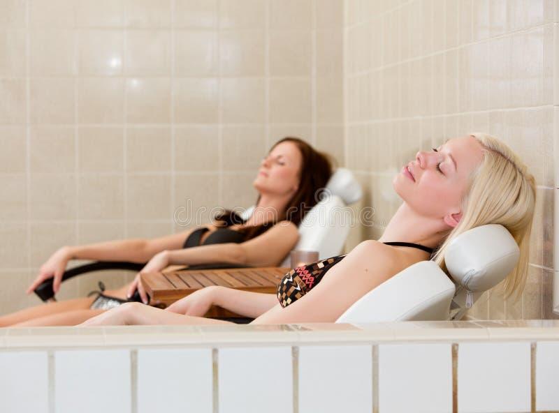 Femme deux détendant au regroupement de station thermale photos stock