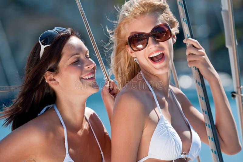 Femme deux de sourire attirante sur le bateau à voiles photos stock