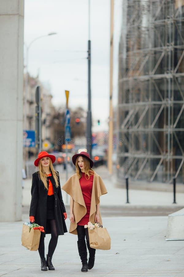 Femme deux occupée marchant sur la rue, parlant les uns avec les autres photos stock