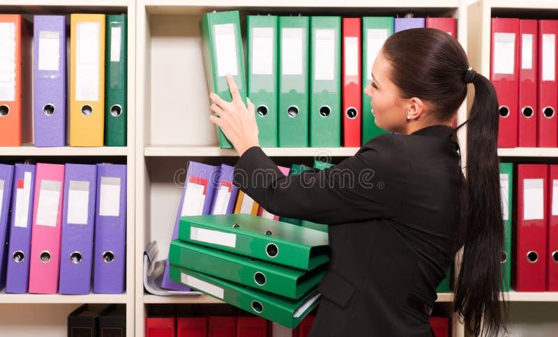 Femme devant des étagères avec des dépliants image stock