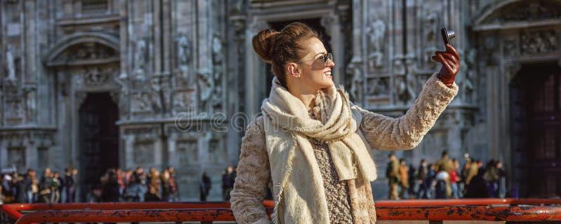 Femme devant le Duomo, Milan avec l'appareil photo numérique prenant la photo image stock