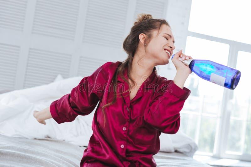 Femme devenant folle feignant la bouteille étant microphone photo stock