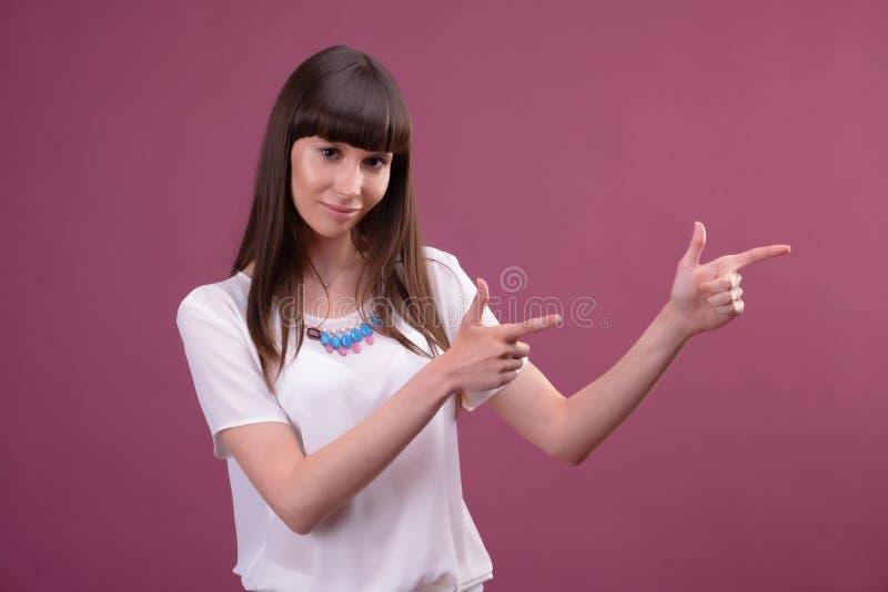 Femme dirigeant le côté de doigt portrait sur le fond de pinl photo libre de droits