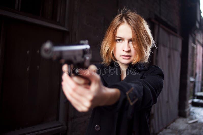 Femme dirigeant une arme à feu Tir de fille de Mafia à quelqu'un sur la rue photographie stock libre de droits