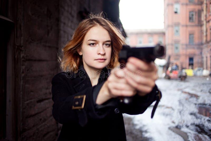 Femme dirigeant une arme à feu Tir de fille de Mafia à quelqu'un sur la rue image stock