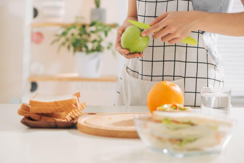 Femme disposant à couper des fruits dans la cuisine pour le dessert images stock