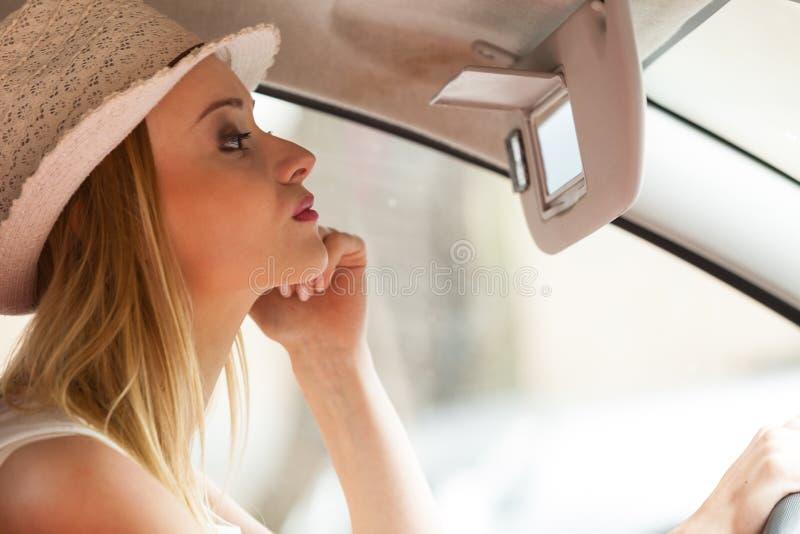 Femme distraite conduisant sa voiture regardant dans le miroir photo stock